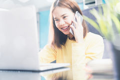 Young woman talking on the phone in modern office, and advise the customer.  royalty free stock images