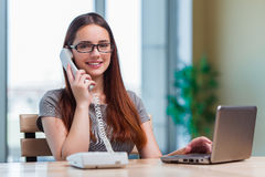 The young woman talking on phone in office. Young woman talking on phone in office Royalty Free Stock Images
