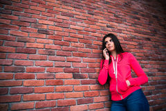 Young woman talking on the phone over brick wall Royalty Free Stock Image