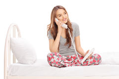 Young woman talking on phone seated on a bed. Beautiful young woman in pajamas, talking on telephone seated on a bed isolated on white background Stock Photo