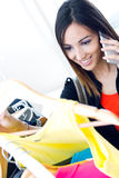 Young woman talking on the phone while shopping for clothes Stock Photography