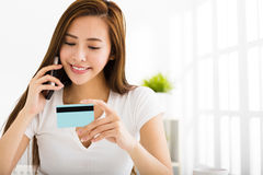 Young woman talking on the phone and showing  credit card Stock Photography