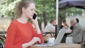 Young Woman Talking on Phone while Sitting in Cafe Terrace stock video