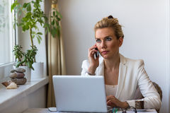 Young  woman talking on phone sitting at a desk with a laptop. Stock Image