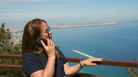 Young woman talking on the phone standing on background the sea. Slow motion. stock footage