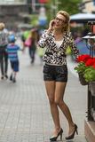 Young woman talking on the phone standing on the street. Royalty Free Stock Image