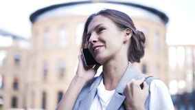 Young woman talking on phone in the street, close up stock video