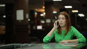 Young woman talking on the phone, a tablet computer lying next to a table stock video footage