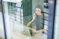 Young woman talking on phone and using tablet computer through the window Royalty Free Stock Image