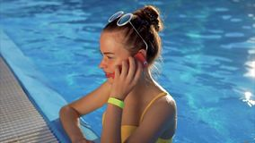 A young woman is talking on the phone in the water, she is calling a friend stock footage