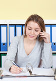 Young woman talking at phone and writing a message Royalty Free Stock Images