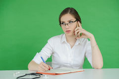 Young woman talking on phone, writing in notebook Royalty Free Stock Photo