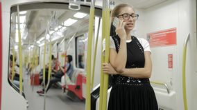 Young woman talking on smart phone in subway.