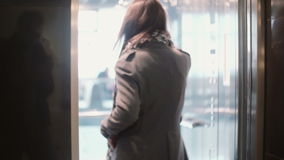 Young woman talking on the smartphone, coming into the elevator and smiling. The lift door is closed. stock video footage