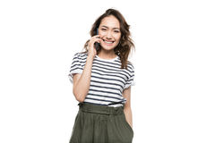 Young woman talking on smartphone and looking at camera Royalty Free Stock Photo