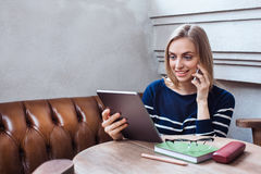 Young woman talking on the smartphone and smiling. Young girl with tablet and sellphone and learns while resting at a. Young woman talking on the smartphone and Royalty Free Stock Photography