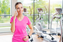 Young woman talking on smartphone. Sport lifestyle and technology. Attractive young woman talking on smartphone in gym Royalty Free Stock Photography