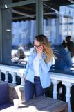 Young woman talking by smartphone and standing at cafe. Young woman talking by smartphone and standing at street cafe. Concept of communicating by phone Royalty Free Stock Photo