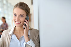 Young woman talking on smartphone at university Stock Photography