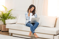 Young woman talking on smartphone and using laptop while sitting on sofa at home Royalty Free Stock Photos