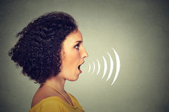 Young woman talking with sound waves coming out of her mouth. Side profile young woman talking with sound waves coming out of her mouth isolated on grey wall Stock Image