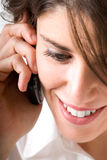 Young woman talking by telephone. And smiling Stock Images