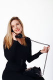 Young Woman Talking on the Telephone. A young woman talking on an old fashion black telephone Royalty Free Stock Photo