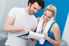 Young woman talking to her fitness trainer. Young women talking to her fitness trainer in the gym smiling as they consult a clipboard charting her progress Royalty Free Stock Images