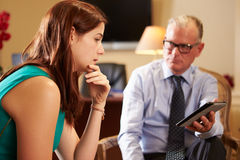 Young Woman Talking To Male Counsellor Using Digital Tablet. Depressed Young Woman Talking To Male Counsellor Using Digital Tablet Sitting Down In Chair royalty free stock photo