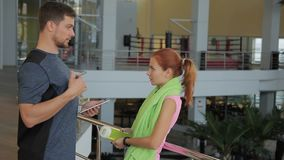 The young woman is talking to male trainer in the modern gym. The man in grey t-shirt explains the sportswoman how to do the exercises showing the position of stock video footage