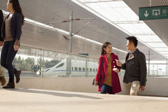 Young woman talking to man on railway platform, China Stock Images