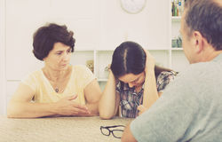 Young woman talking to mature parents. Sad young women talking to mature parents and getting help and support at a home. Focus on mature and young women stock photo