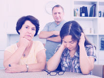 Young woman talking to mature parents. Sad young women talking to her mature parents and getting help and support at home. Focus on mature and young women stock image