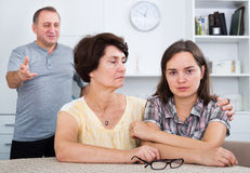 Young woman talking to mature parents. Sad young women talking to her mature parents and getting help and support at the home. Focus on mature and young women stock photography