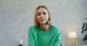 A young woman talking on a video call looking to the camera, frontal shooting