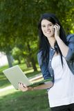 A young woman talks on phone with computer. A young beautiful woman holds a computer outside while talking on the phone stock photo