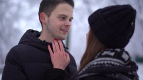 Young woman and tall man looking into each other`s eyes in winter clothing. Woman caress face of boyfriend. Happy couple stock video footage