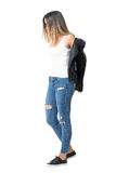 Young woman in tank top and ripped jeans taking off leather jacket Royalty Free Stock Images