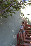 Young woman in tank top and shorts. On the stairs Royalty Free Stock Images