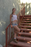 Young woman in tank top and shorts. On the stairs Stock Photos