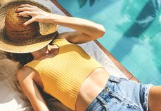 Young woman tanning at poolside royalty free stock image