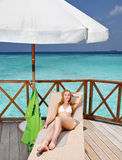 Young woman tans on a terrace of water villa Stock Image