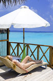 Young woman tans on villa on ocean Maldives Stock Images