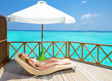 Young woman tans on villa on ocean Maldives