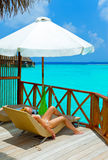 Young woman tans on villa on ocean Maldives Stock Photography