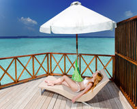 Young woman tans on a water villa terrace Stock Photography