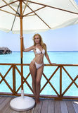 Young woman tans on a water villa terrace , Maldives Stock Images