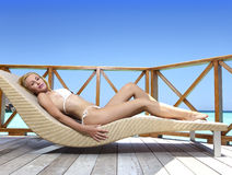 Young woman tans on a water villa terrace , Maldives Stock Photos