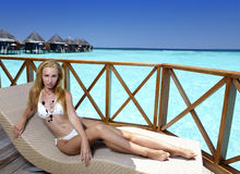 Young woman tans on a water villa terrace , Maldives royalty free stock photography