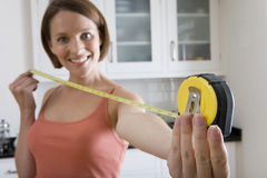 Young woman with tape measure, smiling, portrait, close-up of hand. Young women with tape measure, smiling, portrait, close-up of hand Stock Image